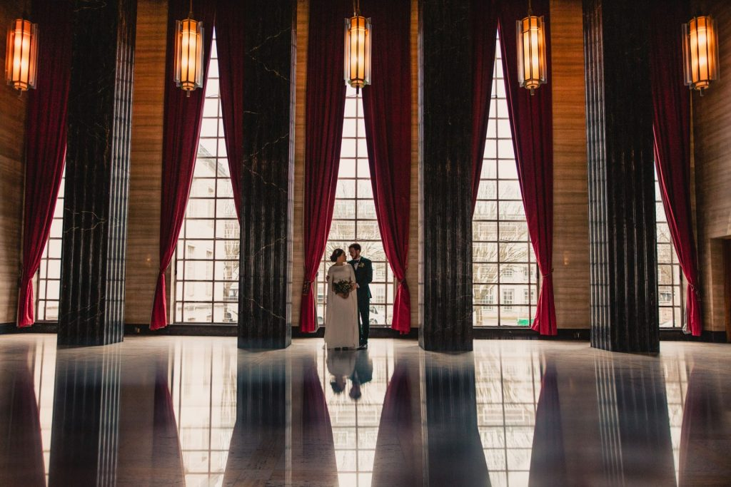 couple standing in the middle window between black marble pillars in the marble hall at temple of peace